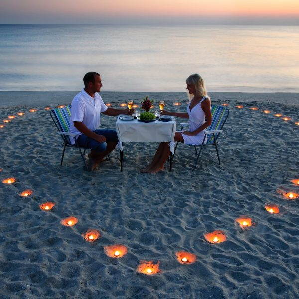 A young lovers couple share a romantic dinner with candles heart on the sea sand beach